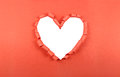 Torn paper heart shaped hole in red with white blank space Stock Photography
