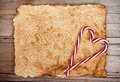 Torn paper onwooden background with candy canes aged on rustic wooden Stock Photography