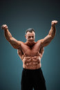 Torso of attractive male body builder on gray background. Royalty Free Stock Photo