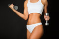 Torso of a young fit woman lifting dumbbells on black background Royalty Free Stock Photo