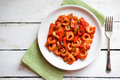 Tortellini primavera parmesan in marinara sauce on wooden rustic Royalty Free Stock Photo