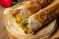 Tortilla wrap mexican with meat and vegetables on wood table Stock Photos