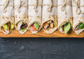 Tortilla wraps with different fillings on dark grey concrete background Royalty Free Stock Photo