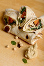 Tortilla wraps with hummus and vegetables on wooden board Stock Photos