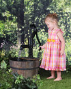 Tot pumping water an adorable year old happily with an old pump on a warm summer day Royalty Free Stock Photos