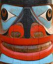 Totem pole face detail of a brightly painted on a Stock Images