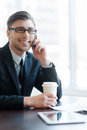 Always in touch cheerful young man formalwear talking on the phone and drinking coffee while sitting at the office Royalty Free Stock Photos