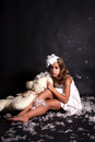Touching a girl angel with a bear and flying feathers on black background Stock Photos