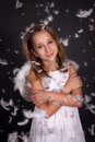 Touching a girl angel with a bear and flying feathers on black background Royalty Free Stock Images