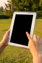 Touching tablet women hand touch screen in the grass field Stock Photos