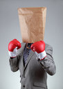 Tough business businessman with paper bag on his head wearing boxing gloves concept for recruitment or anonymous bullying copy Stock Image