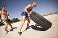 Tough crossfit workout on beach male athlete flipping a truck tire young people doing exercise Stock Photos