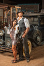 Tough gangster with cute woman handsome muscular s lady in mini skirt Royalty Free Stock Images