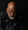 Tough guy in leather strong image of a very man on black Stock Photo