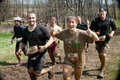 Tough mudder racers having fun getting muddy group of running between obsticles at the competition in mansfield ohio on april this Royalty Free Stock Photo
