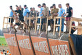 Tough mudder racers jumping off walk the plank male and female obstacle at competition in mansfield ohio on april this Royalty Free Stock Images