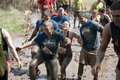 Tough mudder racers in the mud male and female having fun trudging through at competition mansfield ohio on april this race was Royalty Free Stock Images