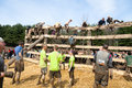 Tough mudder racers waiting to climb the wall male and female climbing over an obstacle at competition in mansfield ohio on april Stock Image