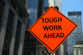 Tough work ahead an orange street sign that reads Royalty Free Stock Image