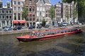 Tour boat in amsterdam holland august large red tourboat a canal and historic houses on august holland Royalty Free Stock Photo