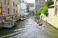 Tour boats on the canal in bruges belgium three loaded with tourists loading platform is left buildings line Royalty Free Stock Image