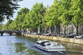 Tourboat in a canal amsterdam center aug tour boat on aug is known as venice of the north it has bridges and canals best way to Royalty Free Stock Images
