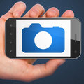 Tourism concept photo camera on smartphone hand holding with display mobile smart phone blue background d render Royalty Free Stock Photo
