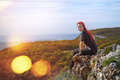 Tourism on top beautiful young girl with red hair sitting the edge of a cliff in the sun Royalty Free Stock Photos