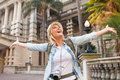 Tourist arms outstretched happy in front of an historical building Royalty Free Stock Photos
