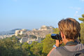 Tourist in athen woman with camcorder takes a picture at acropolis greece Royalty Free Stock Photo