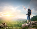 Tourist with backpack enjoy valley view from top of a mountain Royalty Free Stock Photos