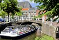 Tourist boat in delft holland july nearing a bridge over a canal july holland Royalty Free Stock Photo