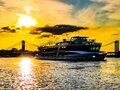 Tourist boat at the riverside of the river Rhein in Cologne with sunlight  on the blue water and clouds Royalty Free Stock Photo