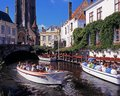 Tourist boat trips bruges view along the dijver with tourists taking in the foreground belgium western europe Stock Photo