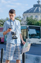 Tourist in bucharest a man uses a mobile phone and a map to look where he is Royalty Free Stock Photos