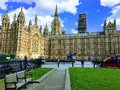Tourist and cars in front of Westminster Houses of Parliament. Royalty Free Stock Photo