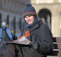 Tourist with city plan on a bench at winter Royalty Free Stock Images