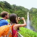 Tourist couple on hawaii taking pictures of the famous akaka falls waterfall on hawaii big island usa happy cheerful young Stock Photography