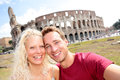 Tourist couple in rome by coliseum on travel taking self portrait photo happy young tourists traveling italy beautiful blonde Stock Photography
