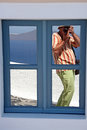 Tourist in firostefani santorini a photographer taking a shot through a window at village island greece Stock Photo