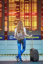 Tourist girl with backpack and carry on luggage in international airport, near flight information board Royalty Free Stock Photo