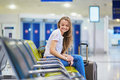 Tourist girl with backpack and carry on luggage in international airport, waiting for flight Royalty Free Stock Photo