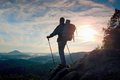 Tourist guide with pole in hand. Hiker with sporty backpack stand on rocky view point above misty valley. Sunny spring daybreak Royalty Free Stock Photo