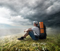 Tourist on the hill resting under storm clouds Royalty Free Stock Photos
