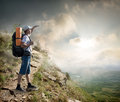 Tourist on the hillside with backpack enjoy valley view from top of a mountain Stock Images