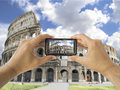 Tourist holds up camera mobile at coliseum in rome takes a picture with his of italy Royalty Free Stock Photo