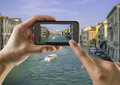 Tourist holds up camera phone at the grand canal takes a picture with his mobile of and basilica santa maria della salute in Royalty Free Stock Photo