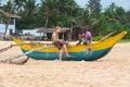 Tourist and local man sitting on a traditional sri lankan fishing boat at beach hikkaduwa lanka february hikkaduwa is great Royalty Free Stock Photos