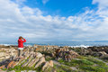 Tourist looking with binocular on the rocky coast line at De Kelders, South Africa, famous for whale watching. Winter season, clou Royalty Free Stock Photo