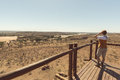 Tourist looking at panorama with binocular from viewpoint over the Mapungubwe National Park, travel destination in South Africa. Royalty Free Stock Photo
